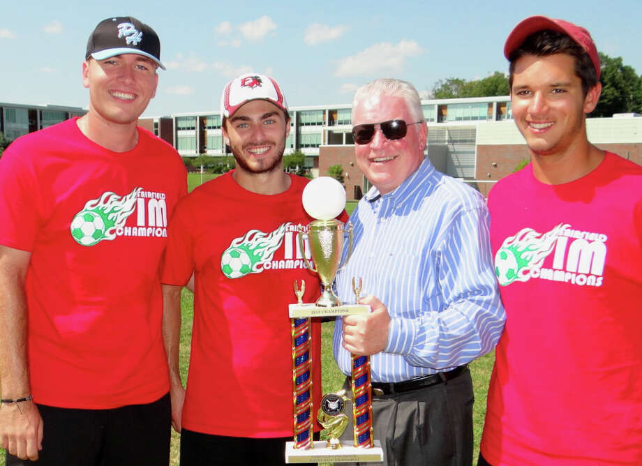 First Selectman Michael Tetreau, second from right, presents the championship trophy and to Fairfield University's John Longo, Matt Finelli and Dennis Turano at the 2nd annual Town Wiffle BallTournament held Saturday at Roger Ludlowe Middle School. Photo: Mike Lauterborn / For Hearst Connecticut Media / Fairfield Citizen