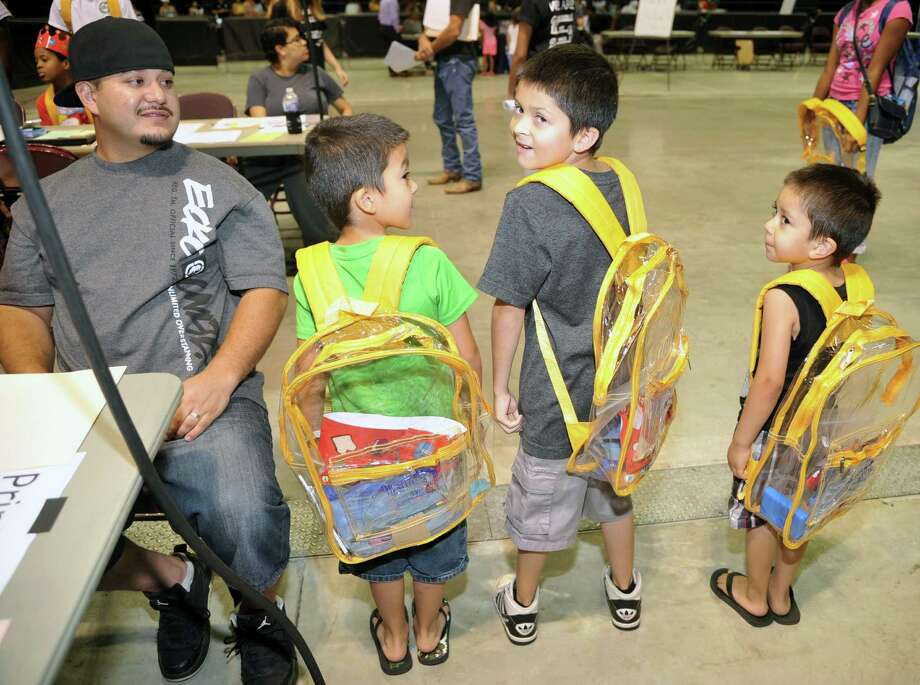 Tomas Chacon watches his sons show off their new backpacks.  Left to right, Tomas, Tony and Carlos.  They will attend Andre Elementary. The family as among 2,000 who attended Cy-Fair ISD's back-to-school expo on Aug. 15 at the Berry Center. Photo: Eddy Matchette, For The Chronicle / Freelance