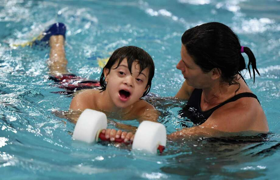Angelfish Therapy co-founder Ailene Tisser assists Adiel Pasarell, 9, in the pool at Camp Move to Learn at Greenwich Catholic School in Greenwich, Conn. Thursday, Aug. 13, 2015.  The two-week camp consists of a variety of active, motor-oriented activities for special needs children age five to 11.  Adiel Pasarell's family came from Puerto Rico and is staying in a hotel for two weeks while Adiel participates in camp. Photo: Tyler Sizemore / Hearst Connecticut Media / Greenwich Time
