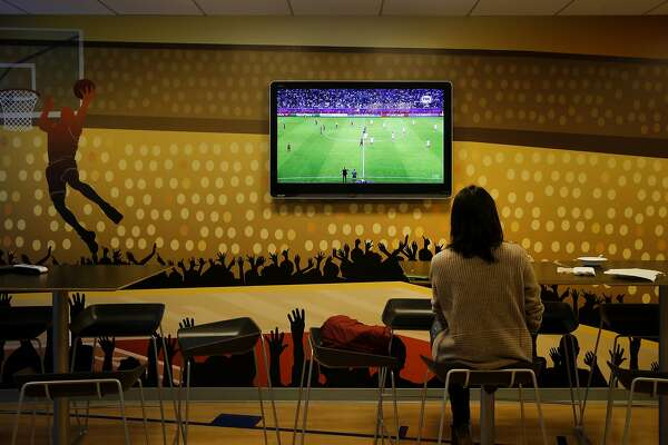 An employee watches a soccer match on television near one of the many kitchen areas at StubHub. The offices of StubHub are off Howard Street in San Francisco, Calif. where they take up several floors over looking the new transit center.