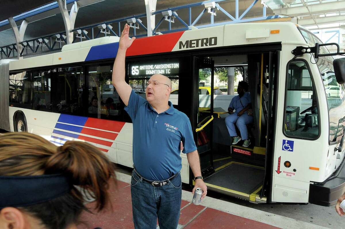 Metro chairman Gilbert Garcia call for his colleagues to gather for a photo in front of a bus at the Downtown Transit Center Sunday August 16, 2015. The group was celebrating the rollout of the new Metro network.(Dave Rossman photo)