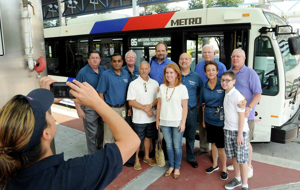 Metro chairman Gilbert Garcia, CEO Tom Lambert and others pose for a photo in front of a bus at the Downtown Transit Center Sunday August 16, 2015. The group was celebrating the rollout of the new Metro network.(Dave Rossman photo)