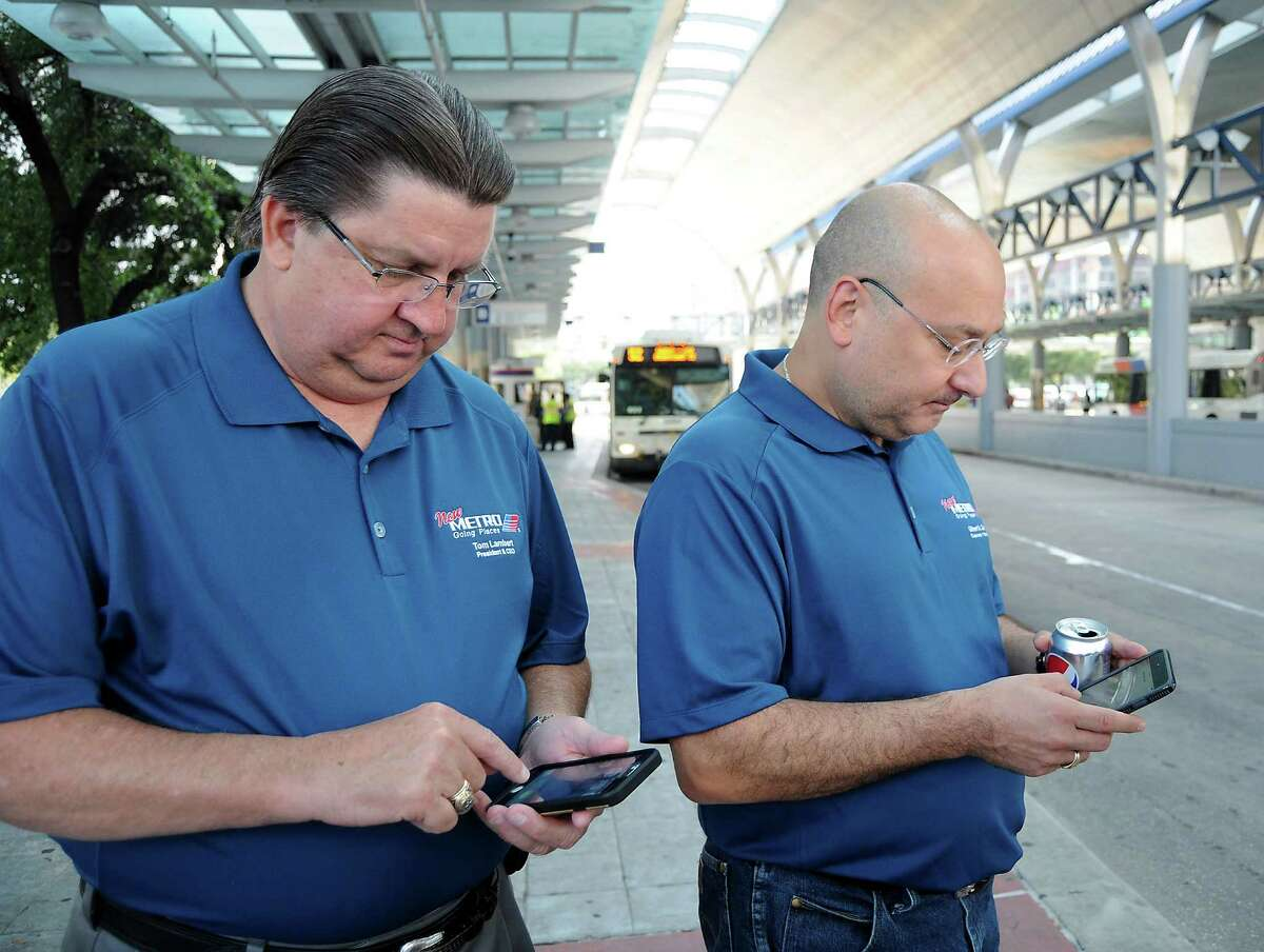 Metro CEO Tom Lambert and then-Metro chairman Gilbert Garcia use the new app to check arrival times for buses at the Downtown Transit Center on Aug. 16, 2015, the first day of a massive redesign of local bus service.