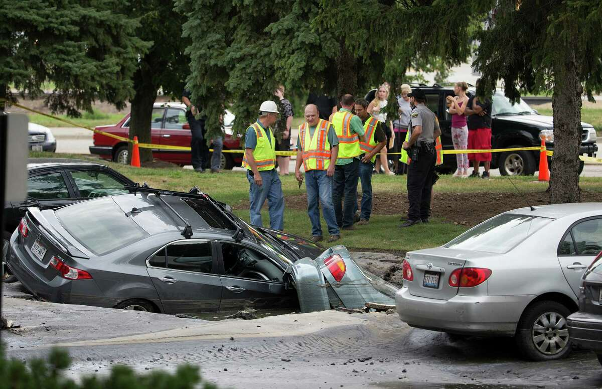 Cars are engulfed in a sinkhole at an apartment complex Friday, Aug. 14, 2015, in Madison, Wis. About 300 residents of the complex were evacuated after a water pipe break created a sinkhole and potential gas leak. (Steve Apps/Wisconsin State Journal via AP)