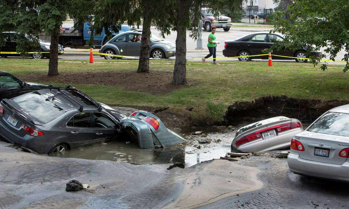 Cars are sumberged in a sinkhole at an apartment complex, Friday, Aug. 14, 2015, in Madison, Wis. About 300 residents of the complex were evacuated after a water pipe break created the sinkhole and potential gas leak. (Steve Apps/Wisconsin State Journal via AP)