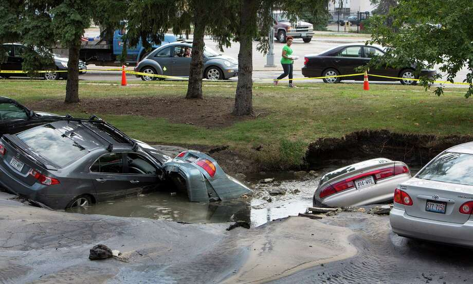 Cars are sumberged in a sinkhole at an apartment complex, Friday, Aug. 14, 2015, in Madison, Wis. About 300 residents of the complex were evacuated after a water pipe break created the sinkhole and potential gas leak. (Steve Apps/Wisconsin State Journal via AP) Photo: Steve Apps, AP  / Wisconsin State Journal