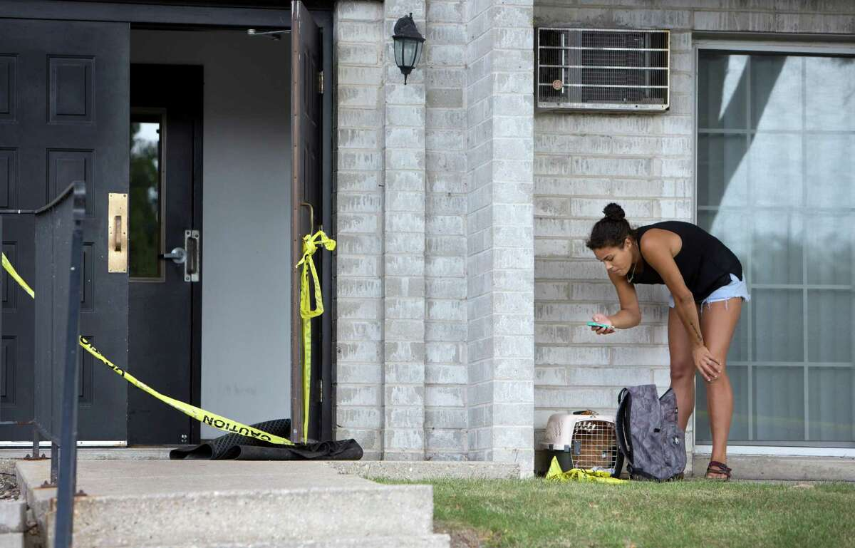 Vanessa Blackwell with her cat Skeddy, prepare to evacuated from their apartment complex after a water pipe break created a sinkhole and potential gas leak, Friday, Aug. 14, 2015, in Madison, Wis. About 300 residents of the complex were evacuated. (Steve Apps/Wisconsin State Journal via AP)