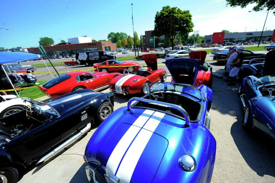 Cars drive past several parked AC Cobras on Woodward near 15 Mile in Birmingham Saturday, Aug. 15, 2015,  during the annual Woodward Dream Cruise. (Steve Perez /Detroit News via AP) Photo: Steve Perez, Associated Press / The Detroit News