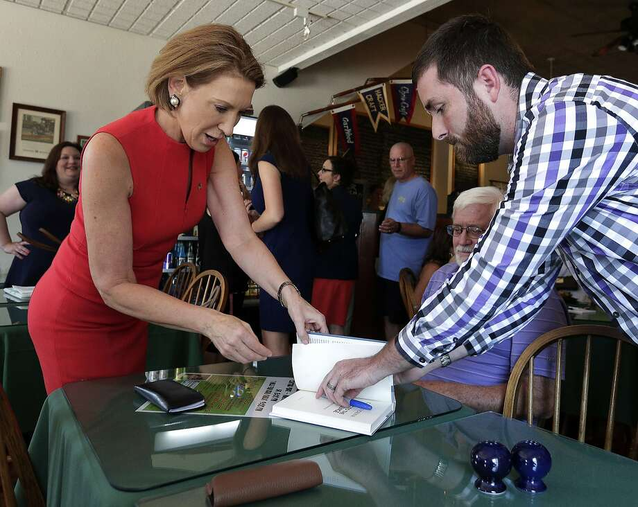 Carly Fiorina signs a book for Tyler Poulter during a cam paign stop Friday at the Starboard Market in Clear Lake, Iowa. Photo: Charlie Riedel, Associated Press