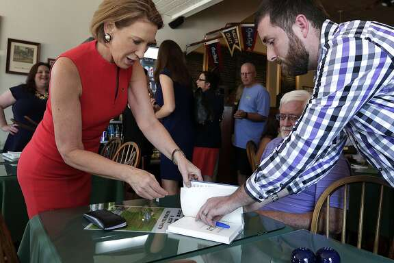 Republican presidential candidate Carly Fiorina signs a book for Tyler Poulter during a campaign stop at the Starboard Market Friday, Aug. 14, 2015, in Clear Lake, Iowa. (AP Photo/Charlie Riedel)