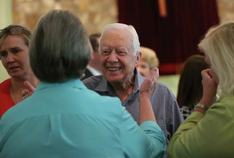 Former President Jimmy Carter reaches to embrace his brother Billy's widow Sybil while greeting family Sunday, Aug. 16, 2015, following service at Maranatha Baptist Church in Plains, Ga. Carter's nieces Mandy Flynn, left, and Jana Carter are also pictured. Sunday at church was emotional because it was the first time many members had seen Carter since his announcement that he has cancer. (Ben Gray/Atlanta Journal-Constitution via AP) Photo: Ben Gray, MBI / The Atlanta Journal-Constitution