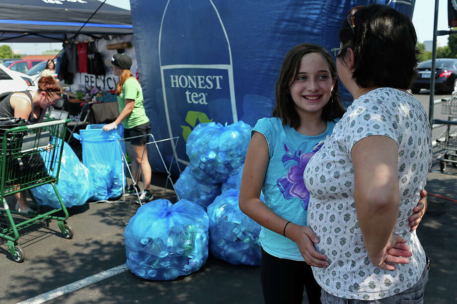 Aurora Stevens, 10, and her mother, Wendy Stevens wait as their load of cans bottles is counted at the Great Recycle on the parking lot of Whole Foods at the Quarry, Sunday, August 16, 2015. Honest Tea and Whole Foods Markets partnered for the two-day event where the public could donate aluminum cans and bottles. The more recycled brought, the more points which can be redeemed for items including iPads, bicycles, wearables, bags, beverages and more. The tour Ð which has been going on for three years Ð is part of Honest TeaÕs efforts to boost recycling rates nationwide. Photo: JERRY LARA, Staff / San Antonio Express-News / © 2015 San Antonio Express-News