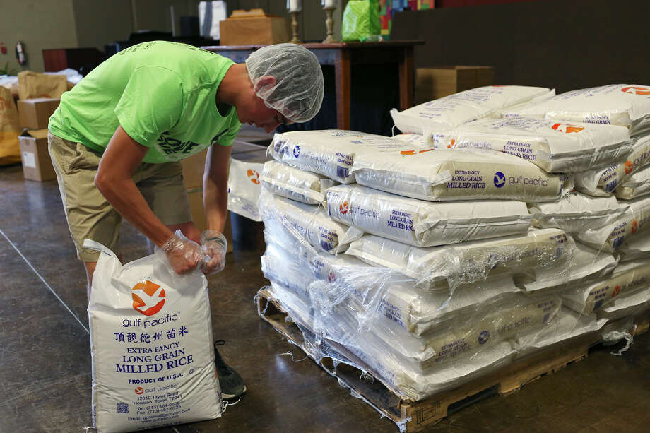 James Sanders, 15, opens a sack of rice as Spring Creek United Methodist Church congregation members gather to prepare over 20,000 meal packages at their main Sanctuary in Fair Oaks Ranch, Sunday, August 16, 2015. The church partnered with Stop Hunger Now, an organization that provides the meals to the world's most vulnerable populations in over 65 countries. The packages were a combination of rice, soy meal, dehydrated vegetables and a packet of season with vitamins and feeds up to six people. Photo: JERRY LARA, Staff / San Antonio Express-News / © 2015 San Antonio Express-News