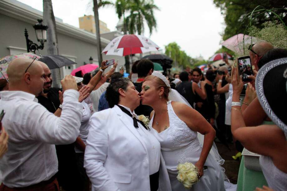 Alma Rosado,left, and Flor Maria Montijo, right, kiss after their wedding during a mass same-sex wedding in San Juan, Puerto Rico, Sunday, Aug. 16, 2015. Over 60 couples from around the region gathered in Puerto Rico's capital to exchange vows at a same-sex marriage ceremony. (AP Photo/Ricardo Arduengo) Photo: Ricardo Arduengo, STR / Associated Press / AP