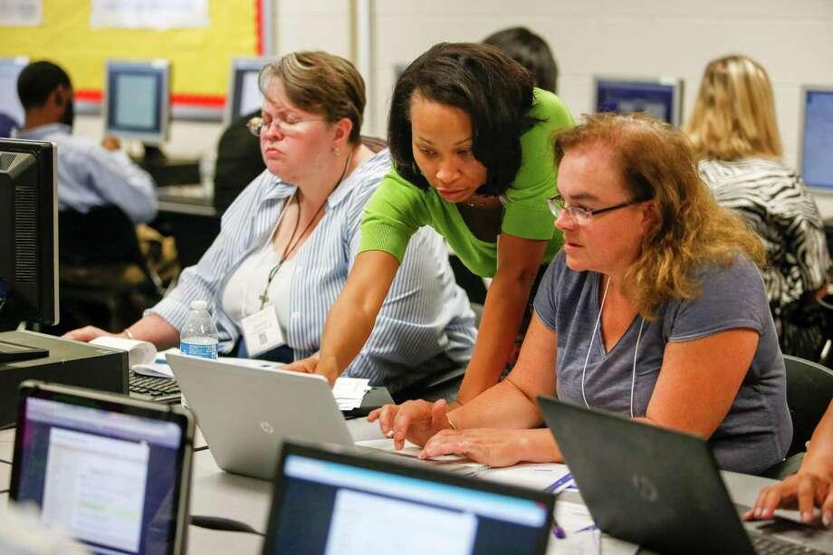 "Stephanie Woodard, center, trains teachers how to use  ""the hub,"" HISD's  online teaching and learning platform, at Caesar Chavez High School.   Photo: Eric Kayne / Eric Kayne"