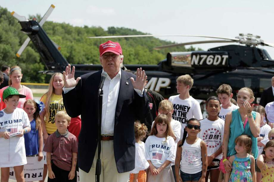 Republican presidential candidate Donald Trump talks to reporters after arriving by helicopter at a nearby ballpark before attending the Iowa State Fair on Saturday in Des Moines. Photo: Charlie Riedel, STF / AP