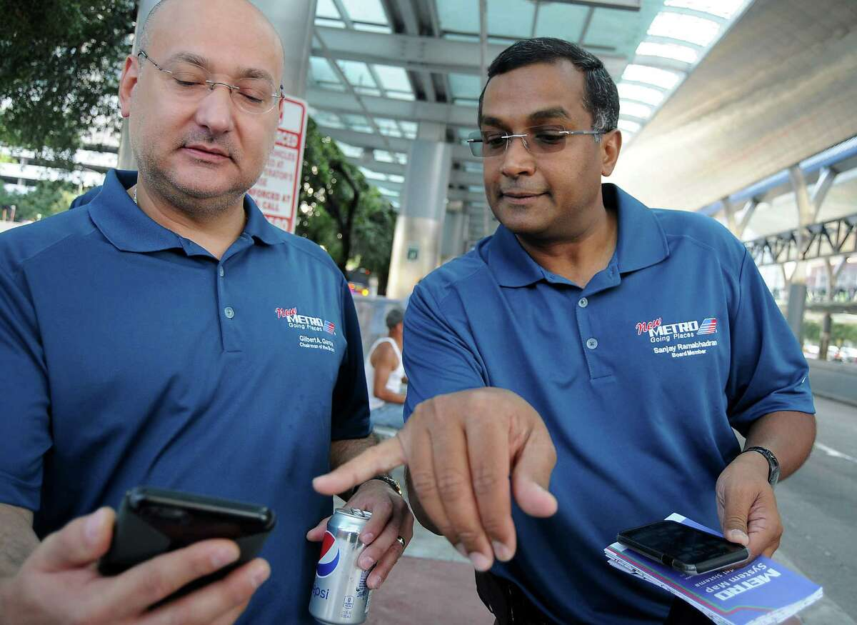 Metropolitan Transit Authority chairman Gilbert Garcia, left, and board member Sanjay Ramabhadran use a new app to check arrival times for buses at the Downtown Transit Center on Sunday. Metro authorities will be posted at various stops to ensure riders can find their way on the new bus route system.