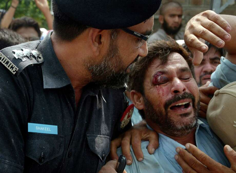 A Pakistani police officer comforts a man recovered from the rubble at the site of a suicide bombing in Shadi Khan, some 80 kilometers (50 miles) northwest from Pakistani capital, Sunday, Aug. 16, 2015.  A pair of suicide bombers detonated their explosives at the home of an anti-Taliban provincial minister, killing him and more than a dozen others in eastern Pakistan, officials said. (AP Photo/Ghulam Shabbir) ORG XMIT: ISL102 Photo: Ghulam Shabbir / AP