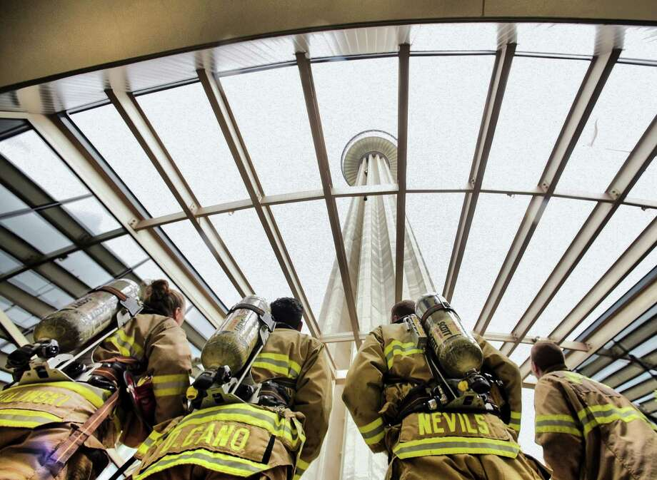 Firefighters Dawn Solinski, left, Daniel Cano, Sam Nevils and Zane Kohler wear full gear as they prepare for a training climb of the stairs within the Tower of the Americas on Friday, July 24, 2015. They will participate in the upcoming San Antonio 110 9/11 Memorial Tower Climb on September 11 in remembrance of the 343 firefighters who died in the attacks on New York City on Sept. 11, 2001. Photo: Billy Calzada, Staff / San Antonio Express-News / San Antonio Express-News