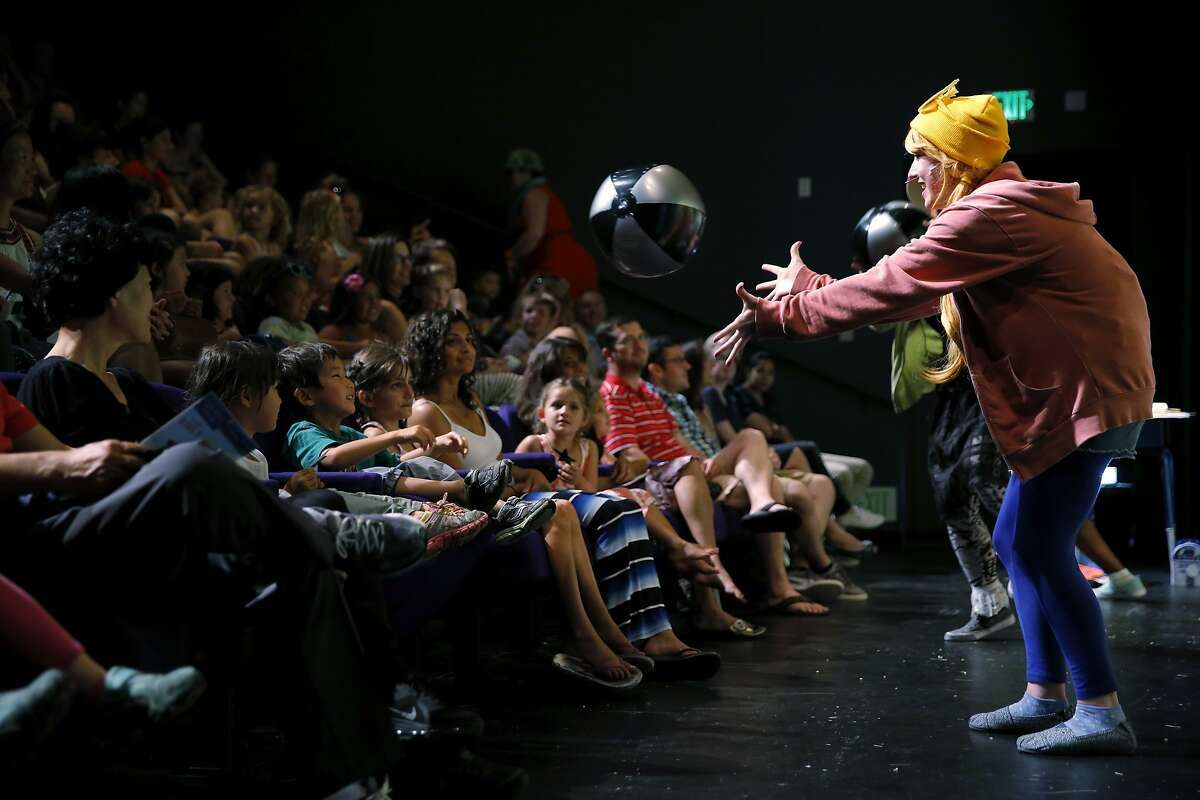Chloe Condon tosses a beach ball to a child in the audience during a performance of