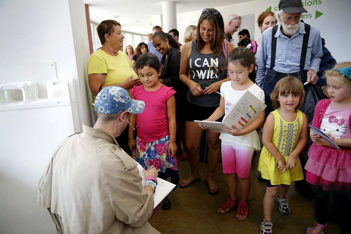 Brett Jones (left) signs autographs for Vanessa Sandoval (center) and Sevanah Sandoval in their copies of the book the play is based off at Creativity Museum Theater in San Francisco, California, on Sunday, Aug. 16, 2015.