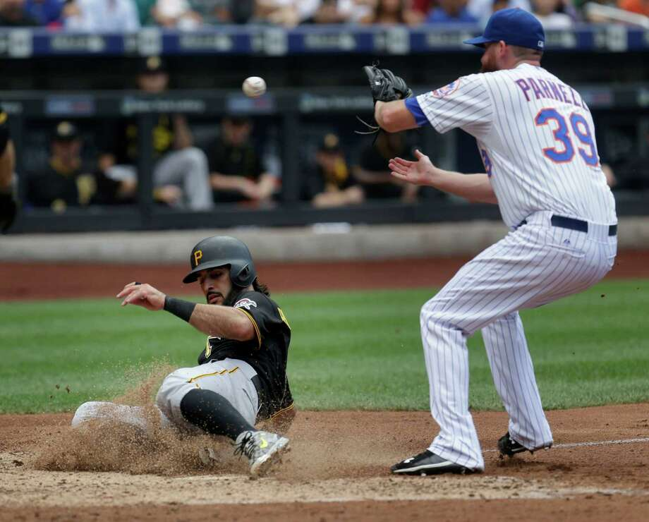 Pittsburgh Pirates' Sean Rodriguez, left, scores past New York Mets relief pitcher Bobby Parnell on a passed ball during the seventh inning of the baseball game at Citi Field, Sunday, Aug. 16, 2015, in New York. (AP Photo/Seth Wenig) ORG XMIT: NYSW110 Photo: Seth Wenig / AP