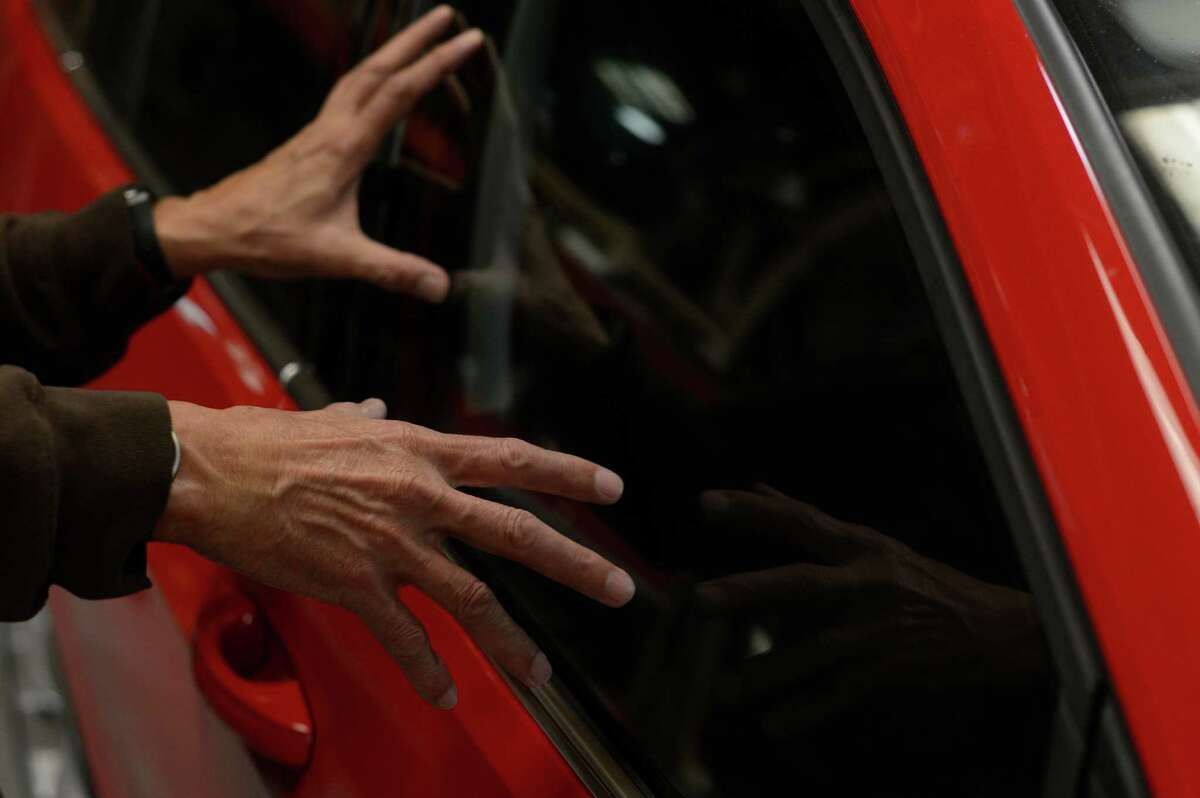Ricky Villareal, sales manager at In and Out Auto Glass, looks into a car that had its front passenger window broken and repaired in San Francisco, California, on Saturday, May 30, 2015.