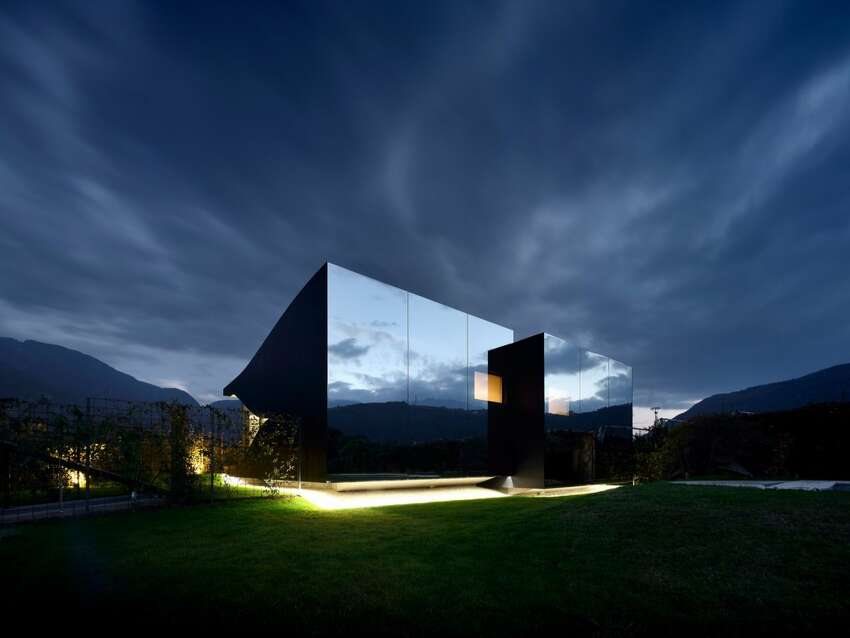 Designed by architect Peter Pichler, these two mirror houses sit side-by-side in the South Tyrolean Dolomites, just outside the city of Bolzano, Italy. The homes were designed as vacation rentals and are available for booking.