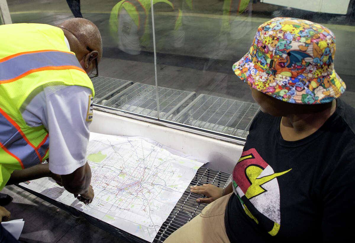 A Metro employee, left, helps Aneshia Remo at the Texas Medical Center Transit Center on Aug. 17.