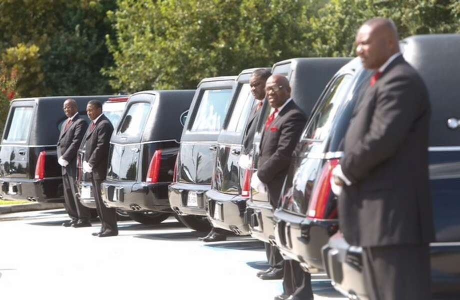 In August, hearses arrived for the funeral services for eight members of the Jackson family, who were shot and killed in their home. Photo: Cody Duty