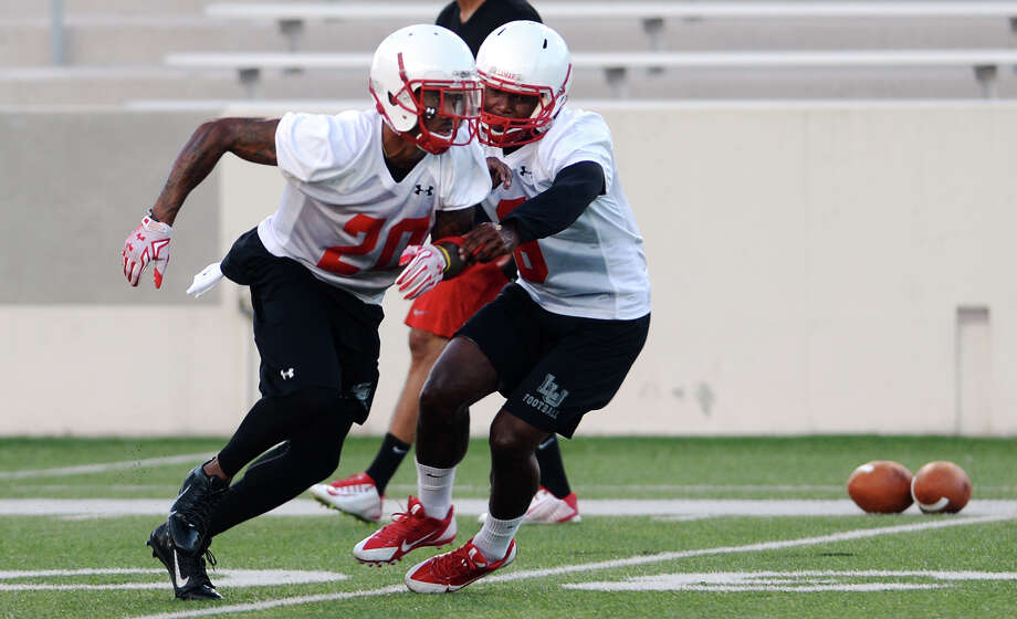 Lamar's Rodney Randle, No. 20, runs through drills with teammate Gratian Gladney, No. 6, on Friday. The Lamar Cardinals held their opening practice Friday evening at Provost Umphrey Stadium.  Photo taken Friday 8/7/15  Jake Daniels/The Enterprise Photo: Jake Daniels / ©2015 The Beaumont Enterprise/Jake Daniels