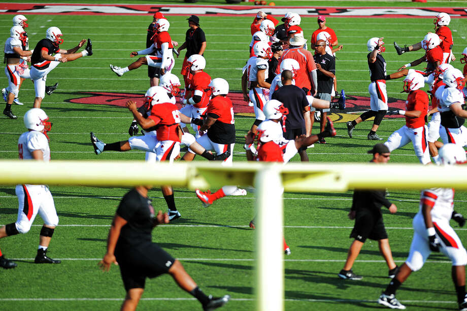 Lamar players stretch out for their scrimmage Saturday. The Lamar Cardinals offense and defense scrimmaged at Provost Umphrey Stadium on Saturday morning. Photo taken Saturday 8/15/15 Jake Daniels/The Enterprise Photo: Jake Daniels / ©2015 The Beaumont Enterprise/Jake Daniels