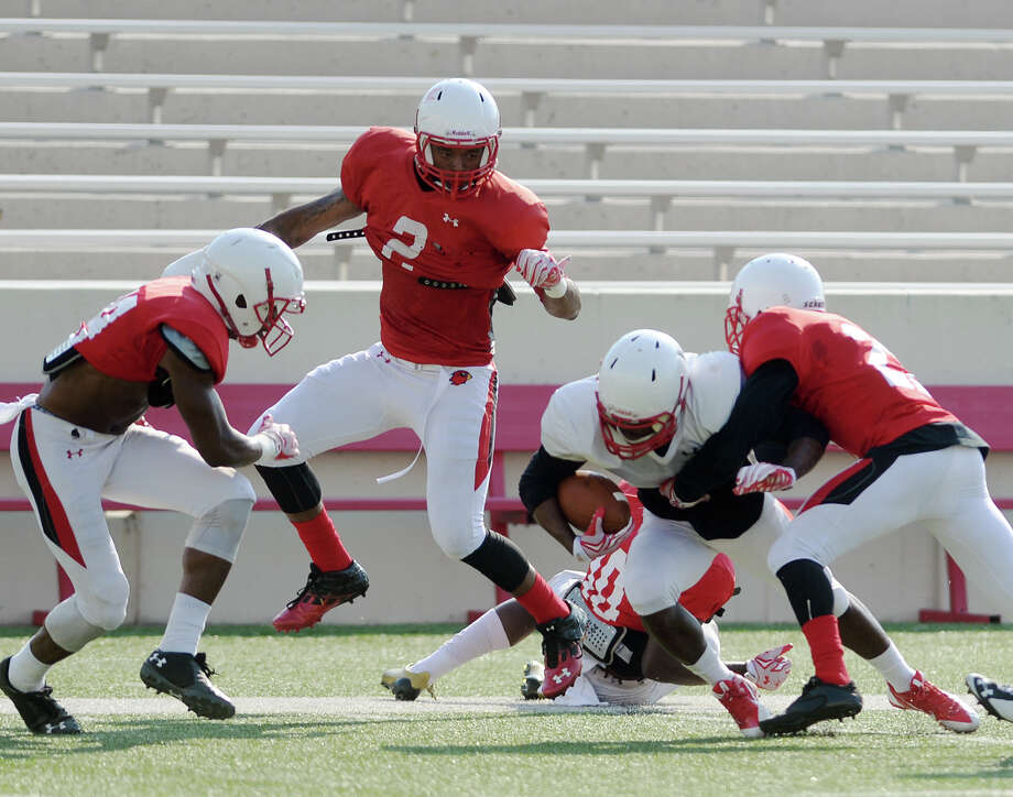 Lamar's Mike Hargis, No. 2, and other defensive players corner a teammate during Saturday morning's practice. The Lamar Cardinals offense and defense scrimmaged at Provost Umphrey Stadium on Saturday morning.  Photo taken Saturday 8/15/15  Jake Daniels/The Enterprise Photo: Jake Daniels / ©2015 The Beaumont Enterprise/Jake Daniels
