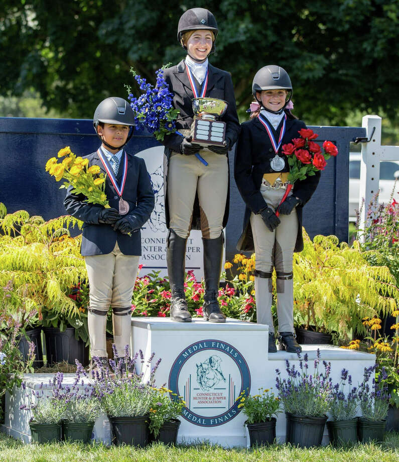Westporter Julia Beck, center, stands atop the winner's podium after winning the CHJA Children's Hunter Pony Classic at Fairfield County Hunt Club in Westport, Connecticut last weekend. Photo: Contributed Photo / Westport News Contributed