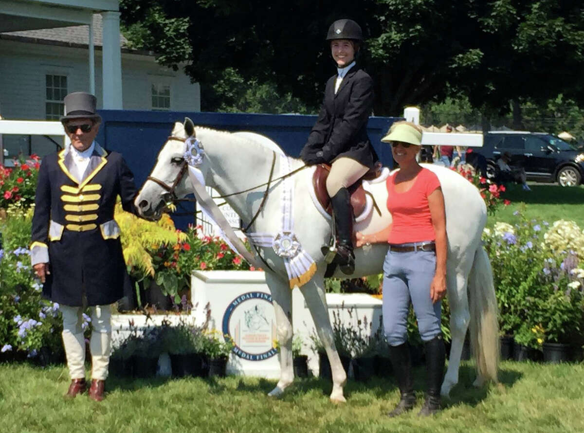 Julia Beck, center, and her trainer Donna Pace, right, of Nautilus Farm placed fourth in the CHJA Children's Medal Finals out of 65 competitors at the Fairfield County Hunt Club in Westport, Connecticut last weekend.