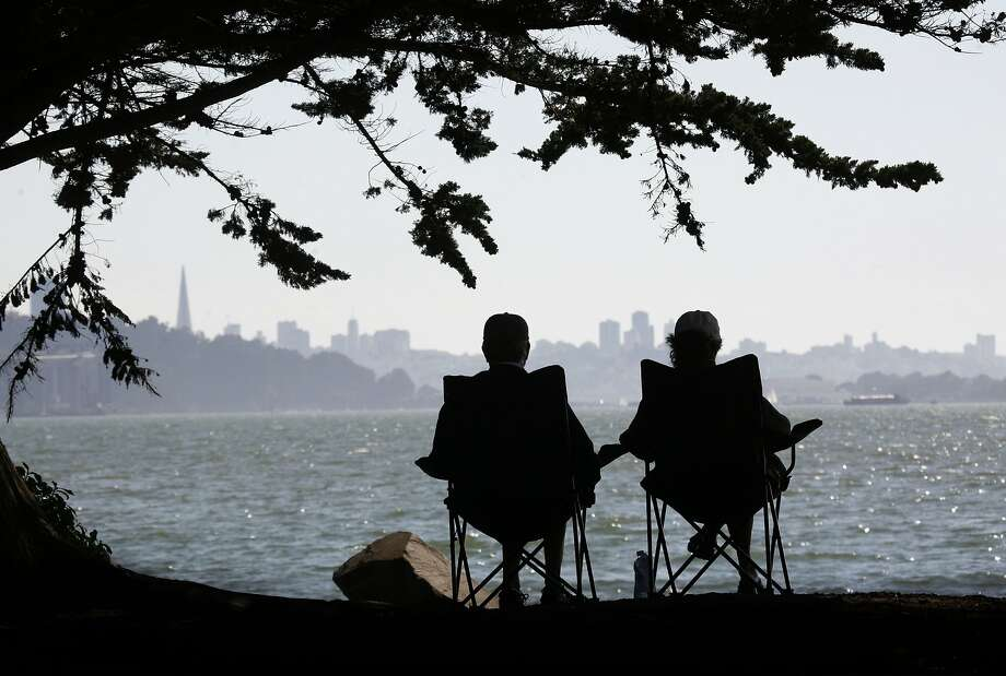 In this file photo Steve and Eldem Rank of Concord had it made in the shade near the Emeryville marina with their million dollar view of the city and the bay. Hot weather is expected to arrive in the Bay Area this week. Photo: Michael Maloney, The Chronicle