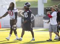 """Houston Texans outside linebacker Jadeveon Clowney (90) and wide receiver DeAndre Hopkins (10) walk onto the practice field followed by """"Hard Knocks"""" cameras during Texans training camp at the Methodist Training Center Monday, Aug. 17, 2015, in Houston. Clowney practiced for the first time Monday, since his season-ending micro fracture surgery last season. ( Brett Coomer / Houston Chronicle )"""
