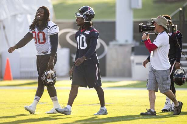 "Houston Texans outside linebacker Jadeveon Clowney (90) and wide receiver DeAndre Hopkins (10) walk onto the practice field followed by ""Hard Knocks"" cameras during Texans training camp at the Methodist Training Center Monday, Aug. 17, 2015, in Houston. Clowney practiced for the first time Monday, since his season-ending micro fracture surgery last season. ( Brett Coomer / Houston Chronicle )"