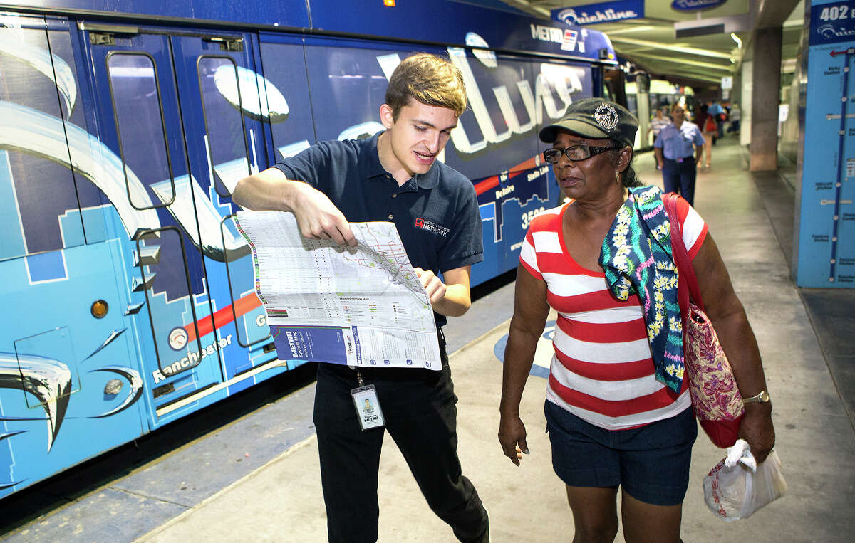 Metro employee Barrett Ochoa, left, helps rider Sophia Morgan, find her route Monday at the Texas Medical Center Transit Center.