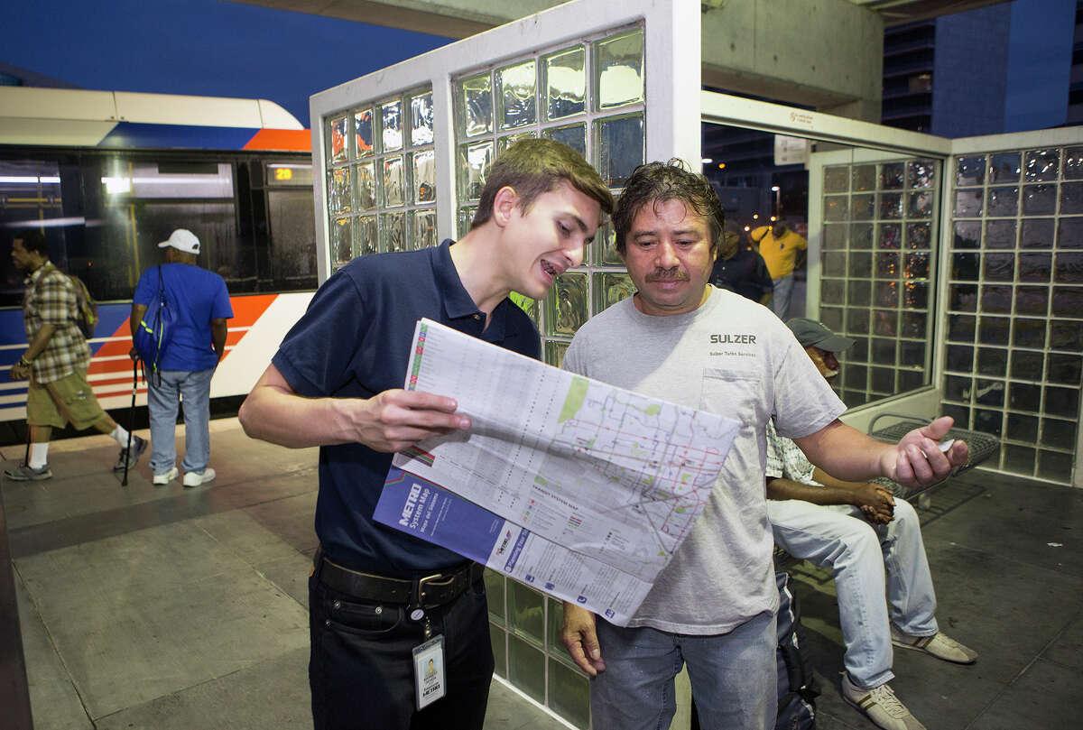 Ochoa helps rider Alberto Quintanilla, right, find his route at the Texas Medical Center Transit Center.
