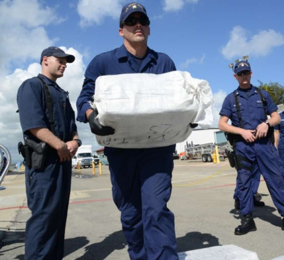 A Coast Guardsman assists with offloading approximately 1,230 pounds of cocaine in San Juan, Puerto Rico, Aug. 14, 2015. Adm. Karl Schultz said crews have seized 1.3 million pounds (0.6 million kilograms) of cocaine in the last few years.