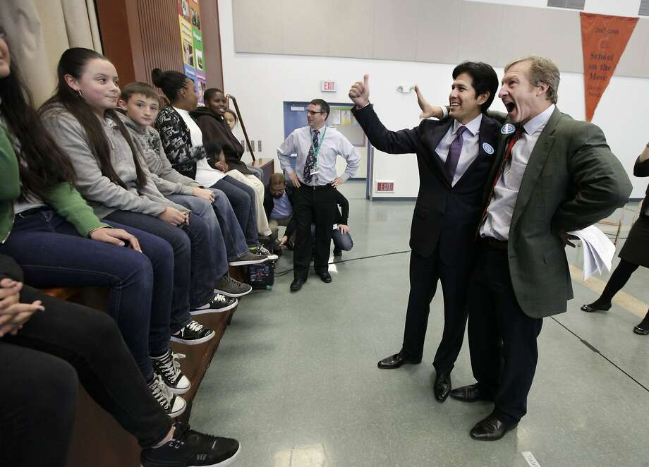FILE -- In this Dec. 4, 2012 file photo, Proposition 39 co-chairs Sen. Kevin de Leon, D-Los Angeles, second from right, and billionaire financier Tom Steyer, right, joke with youngsters from the Mark Twain Elementary School where a proposed bill to fund energy efficiency projects at schools in California's poorest communities was unveiled in Sacramento, Calif. Three years after California voters passed a ballot measure to raise taxes on corporations and generate clean energy jobs by funding energy-efficiency projects in schools, barely one-tenth of the promised jobs have been created.(AP, according to a review by The Associated Press (AP Photo/Rich Pedroncelli,file) Photo: Rich Pedroncelli, Associated Press