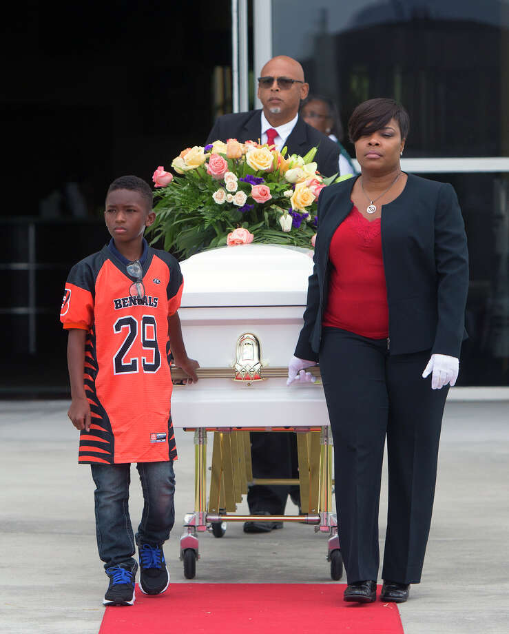 Teammate of Nathaniel's football team, Darius Rogers, 10, accompanies a casket to a hearse after a memorial service at Fallbrook Church, Monday, Aug. 17, 2015. David Conley, the father of one of the children, faces capital murder charges from the shooting. Killed in the Aug. 8 shooting were: Conley's former domestic partner, 40-year-old Valerie Jackson; her husband, 50-year-old Dwayne Jackson; 13-year-old Nathaniel, 11-year-old Honesty, 10-year-old Dwayne, 9-year-old Caleb, 7-year-old Trinity and 6-year-old Jonah. Authorities say Nathaniel was Conley's son with Valerie Jackson. Photo: Cody Duty, Houston Chronicle / © 2015 Houston Chronicle