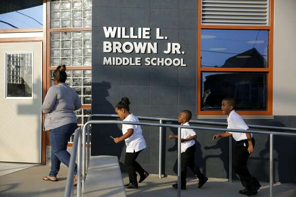 A mother and three children rush into Willie L. Brown Jr. Middle School during the first day of school in San Francisco, California, on Monday, Aug. 17, 2015.