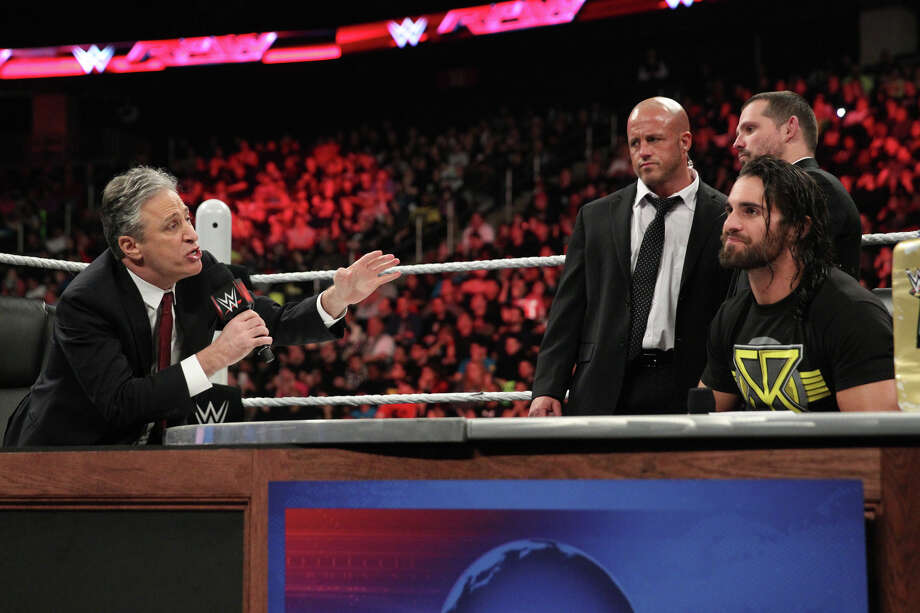 Jon Stewart makes an appearance with professional wrestler Seth Rollins on WWE's Monday Night Raw earlier this year. WWE announced Monday that Stewart will host SummerSlam in Brooklyn on August 23.PHOTOS: Past WWE Champions – where are they now? Photo: ©2015 WWE, Inc. All Rights Reserved.
