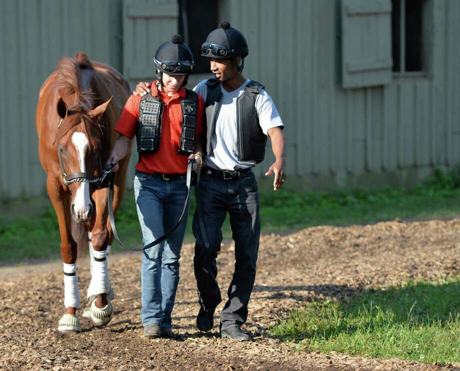 Apprentice jockey to-be, Lane Luzzi, who just finished jockey training school,  left gets some friendly advice from journeyman jockey Kendrick Carmouche Monday morning Aug. 17, 2015 at the Oklahoma Training Center in Saratoga Springs, N.Y.     (Skip Dickstein/Times Union) Photo: SKIP DICKSTEIN