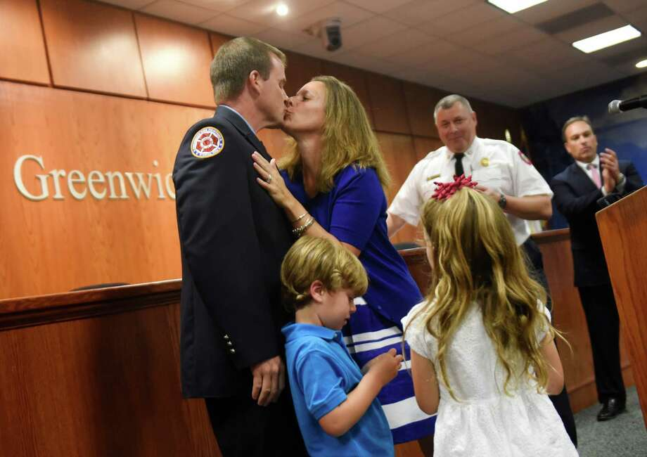 Matthew Brooks kisses his wife, Kristen, as his children, Finn, 5, and Regan, 6, join him up front after being sworn in as a Lieutenant during the Greenwich Fire Department promotional ceremony at Town Hall in Greenwich, Conn. Monday, Aug. 17, 2015.  A 10-year veteran, Brooks is a union secretary and instructor who has been working on long-range planning issues in the department. Photo: Tyler Sizemore / Hearst Connecticut Media / Greenwich Time