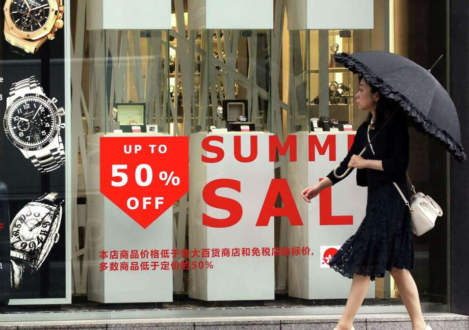 A Tokyo jewelry store offers bargains Monday, on a day when Japan announced a shrinking gross domestic product that sent global oil prices down. (Yoshikazu Tsuno/AFP/Getty Images) Photo: YOSHIKAZU TSUNO, Staff / AFP