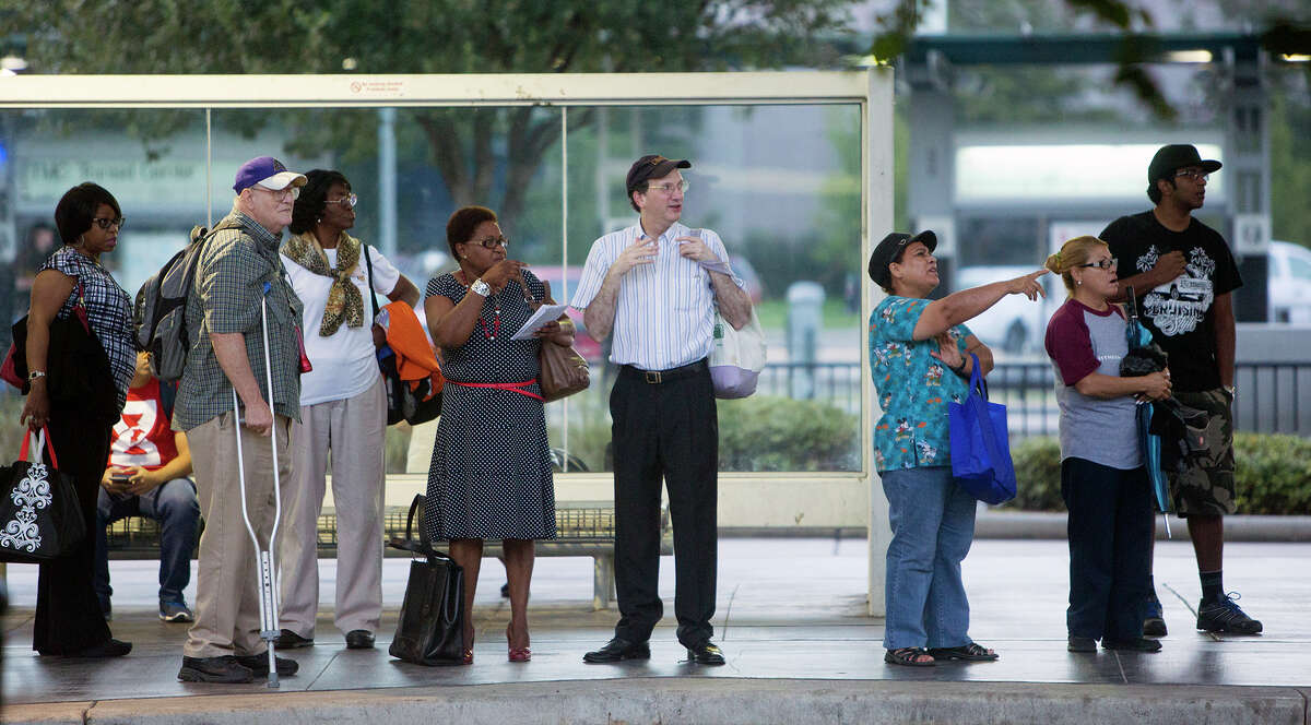 Riders wait for their bus at the Texas Medical Center Transit Center Monday. With local bus and train rides free this week, many hopped aboard just to check things out.
