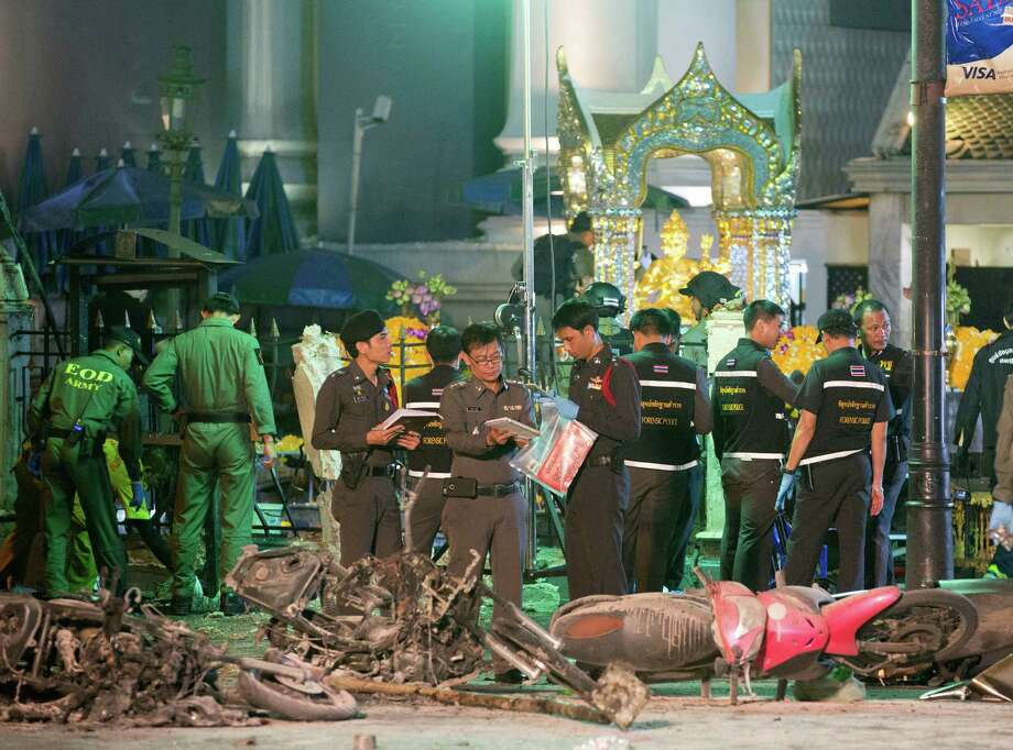 Police investigate the scene at the Erawan Shrine after an explosion in Bangkok, Thailand, on Monday killed a number of people and injured others. Photo: Mark Baker, STF / AP